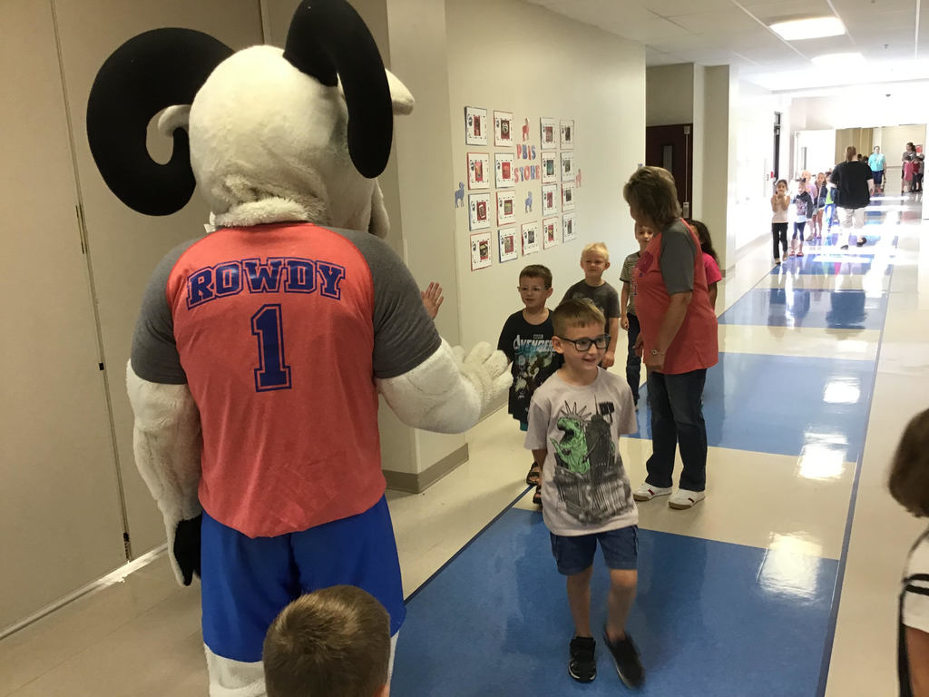 Rowdy the Ram giving high fives to students in line