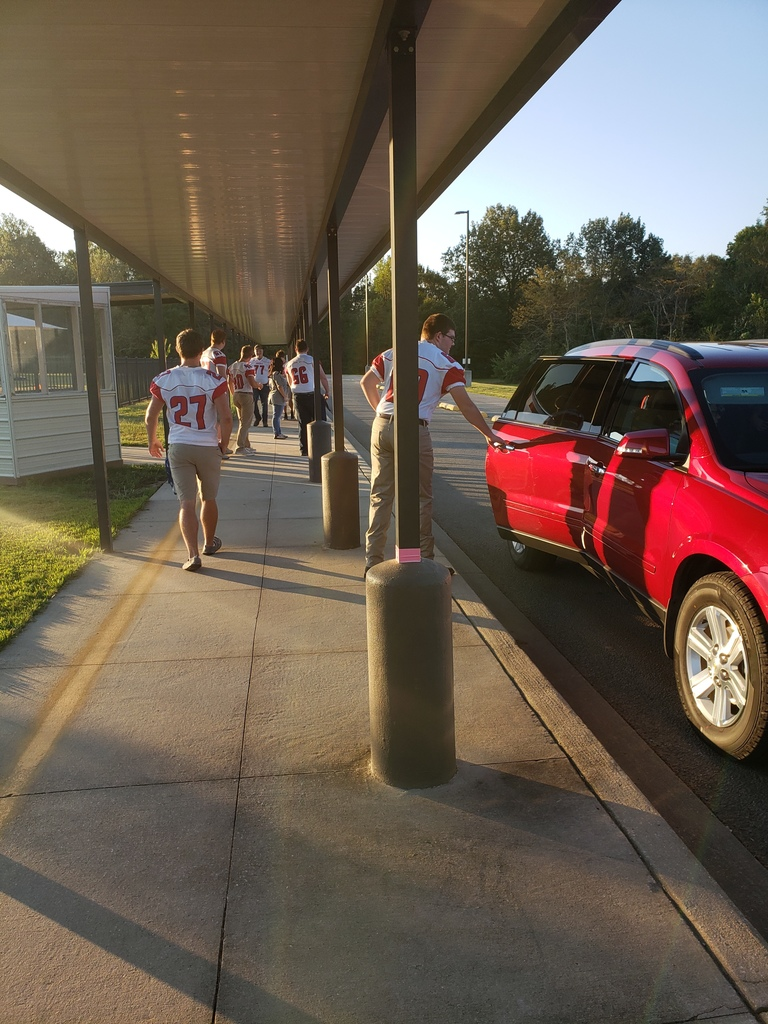 Football Players helping with car line